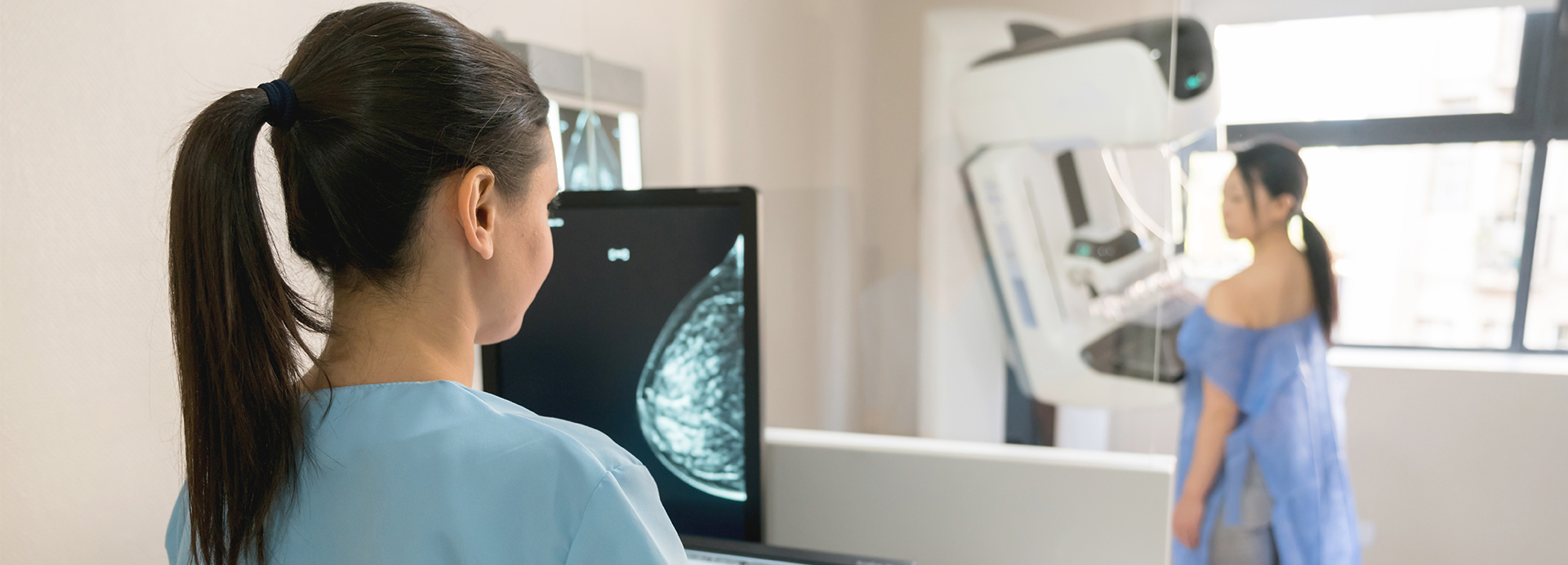 Medical Technician performing a mammogram on a patient