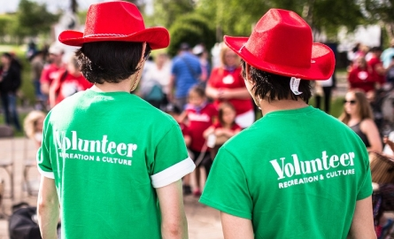 Two volunteers showing their volunteer tshirts at an event
