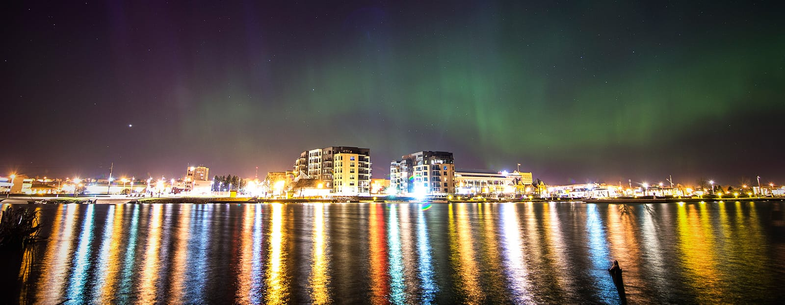 Northern Lights over city waterfront