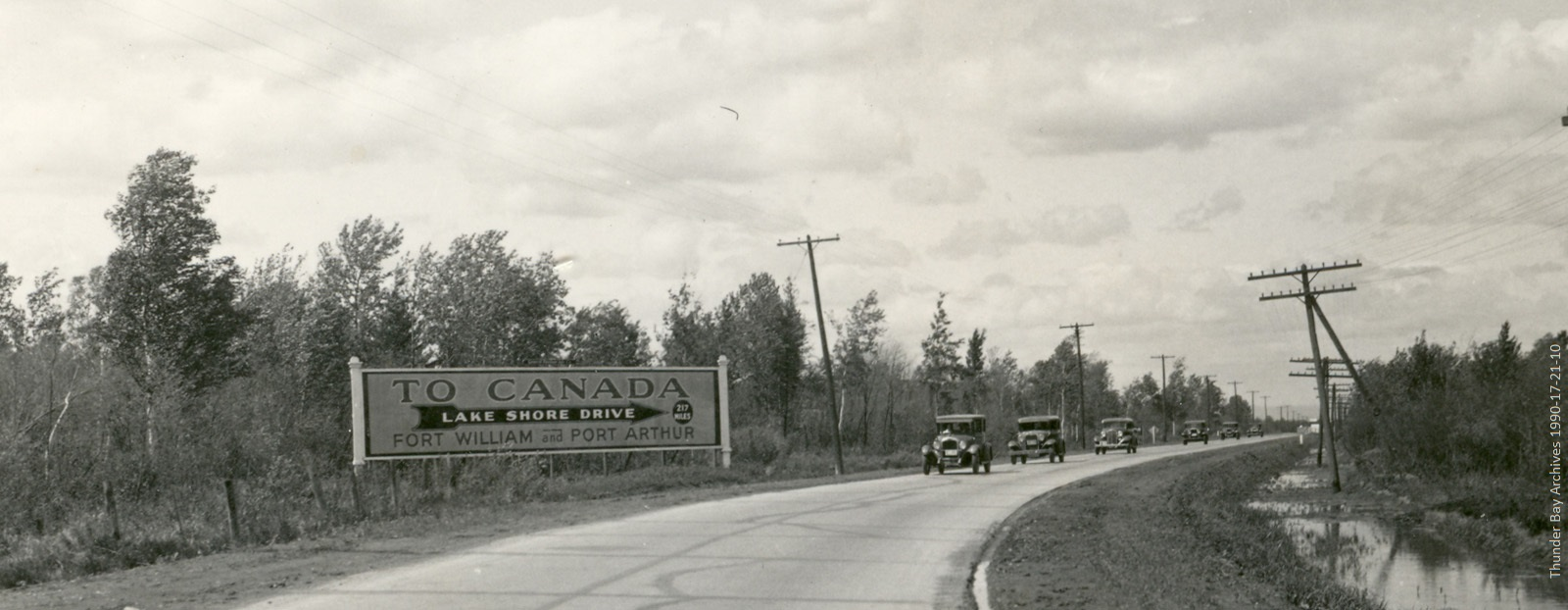black and white photo of a road sign to Port Arthur and Fort William and old cars on driving on road
