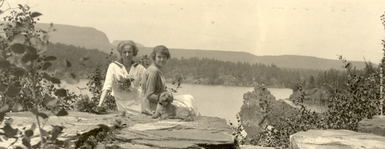 black and white photo of 1910s women and dog sitting on rock overlooking water