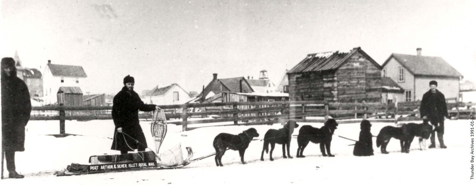 black and white photo of men in snow with dogs sled in front of houses