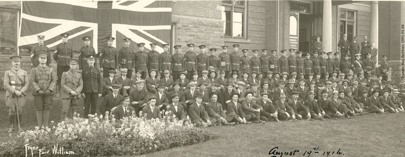 group portrait of WWI soldiers in front of Union Jack flag