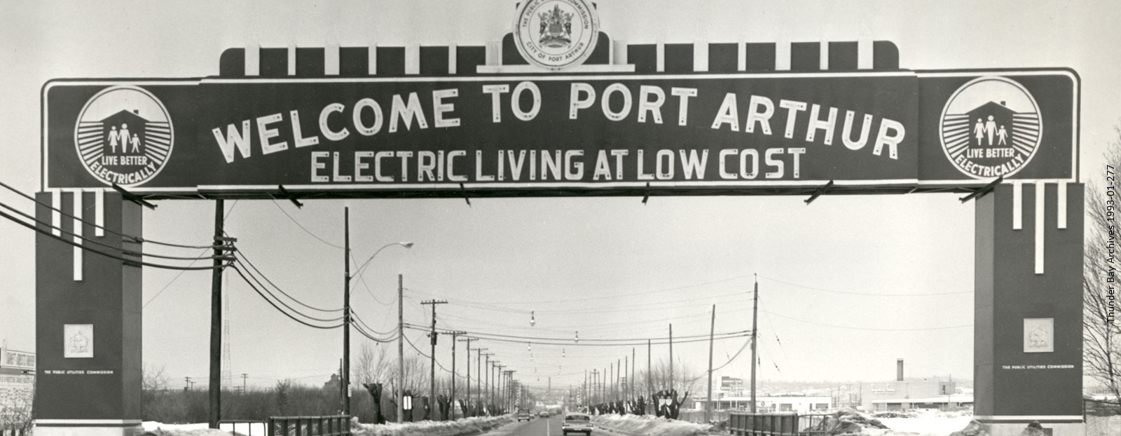 black and white photo of archway over road with sign for Port Arthur