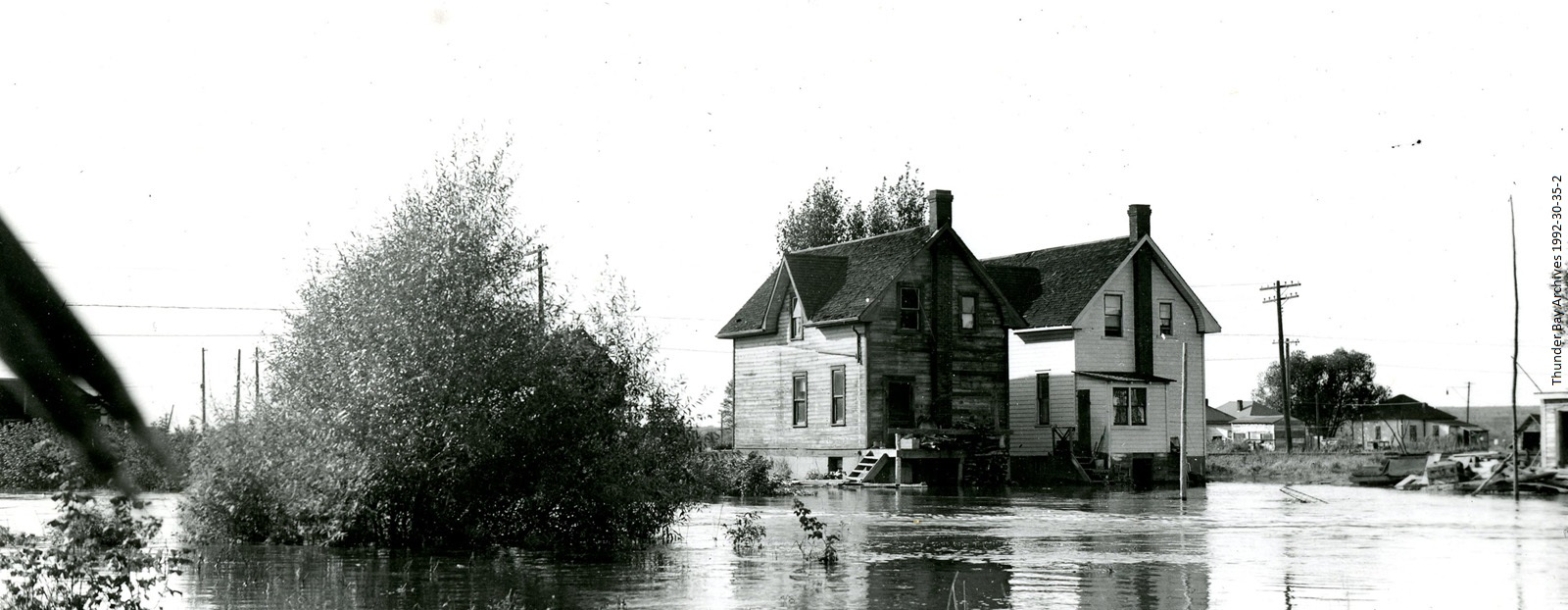 Two houses sit in a field of water after a flood