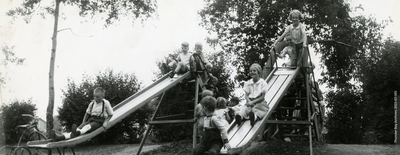Young children play on two slides in a park
