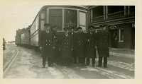 A group of men stand in front of a trolley car