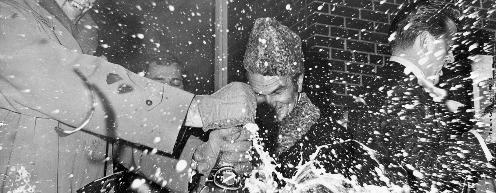 Four men are shown smashing a bottle of champagne as it sprays