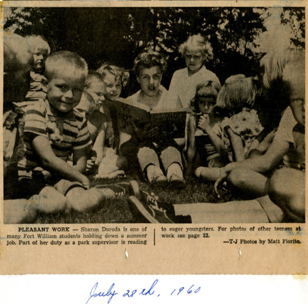 A group of children gather around an adult holding a book