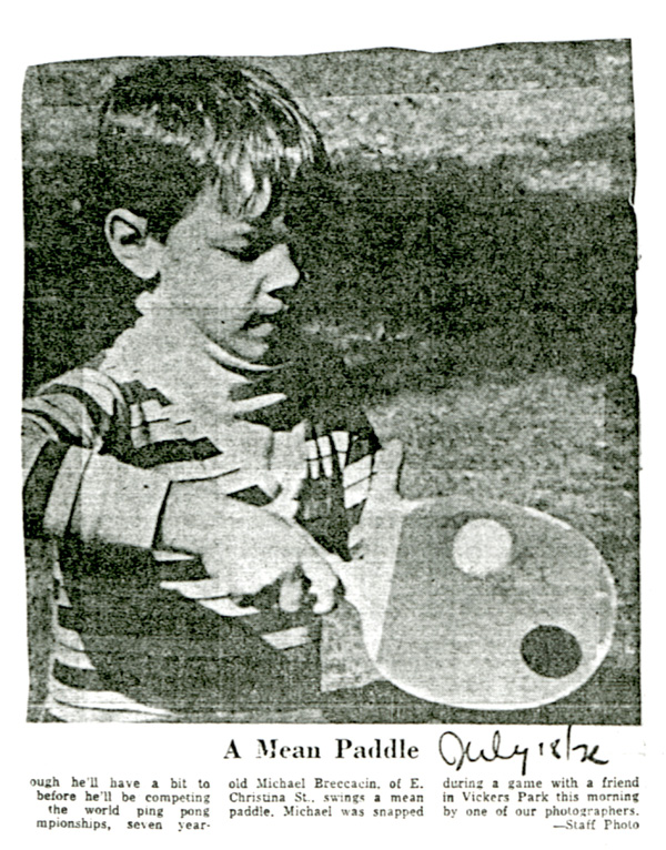 A young child is shown holding a paddle in motion to hit a ball
