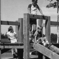 Children play on a slide in a black and white photograph
