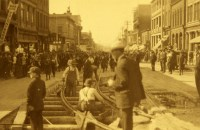 a crowd of people stand on railway tracks in a sepia photograph