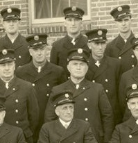 A group of men in firefighter uniforms sit together