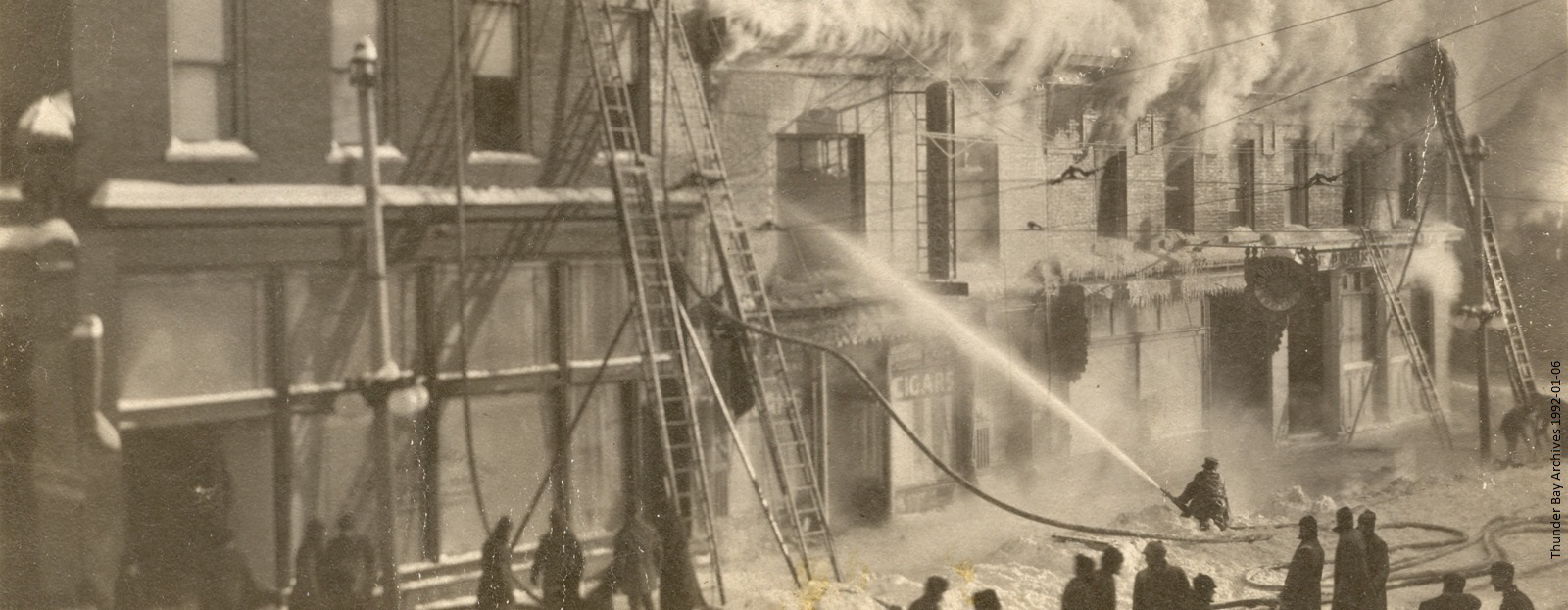 A group of firefighters extinguish a fire using ladders and hose