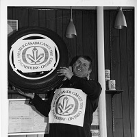 A man holds a branded tire with the Canada Games logo