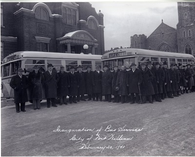 Conductors and workers stand infront of newly built gas buses