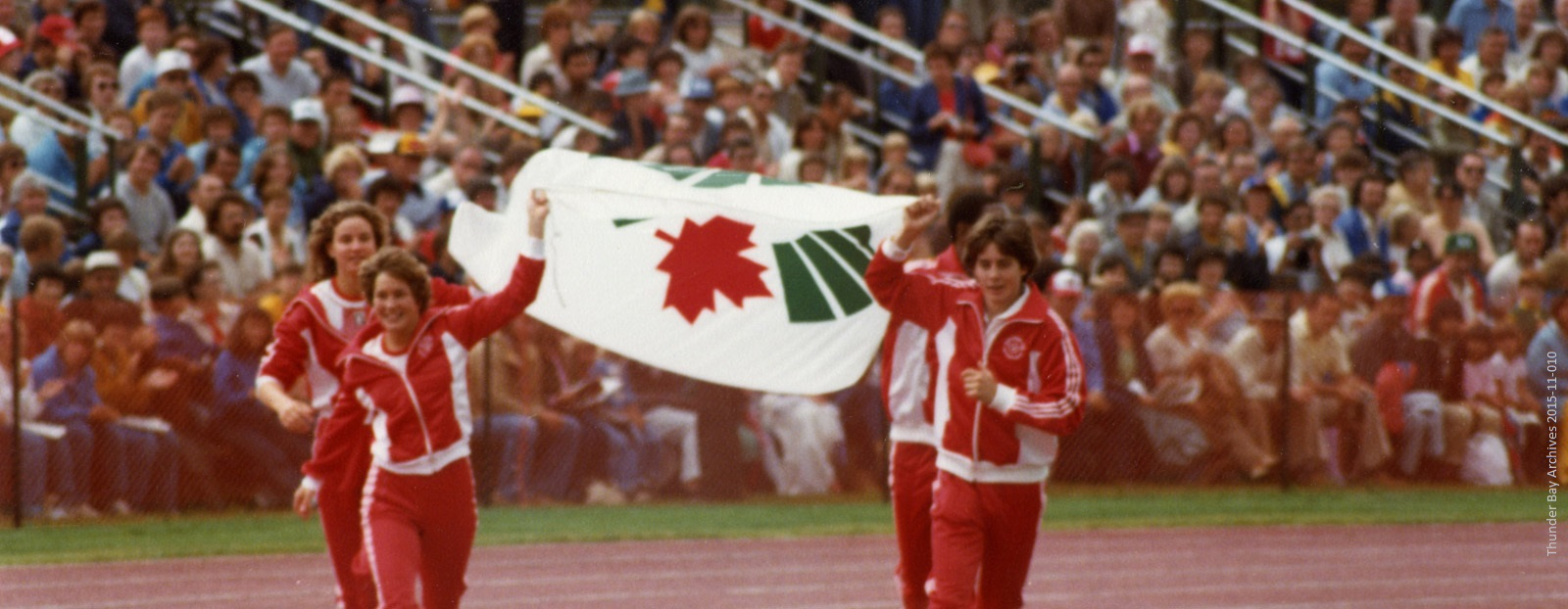 A group of athletes wearing red run with a flag held between the lead pair