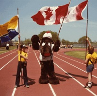 Two children stan on either side of a brown moose mascot holding flags