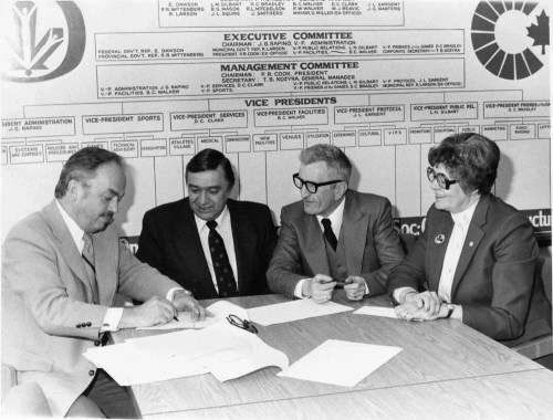 Four people sit at a table preparing to sign a document