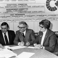A group of people sit around a table ready to sign a paper
