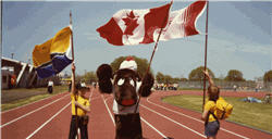 Two children hold flags with a person wearing a moose costume in between