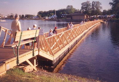 A wooden bridge is built across the water with people walking along