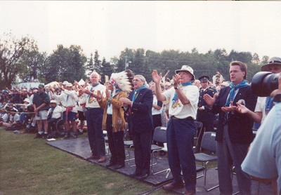 A line of men stand clapping with some wearing regalia