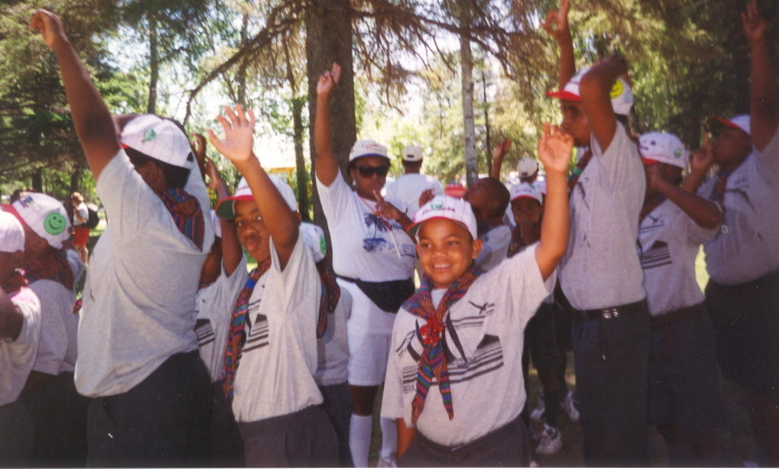 A group of scouts luagh and put their hands up in front of trees