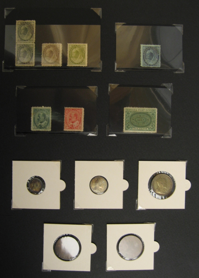 A black sheet with various small coins and stamps taped to it