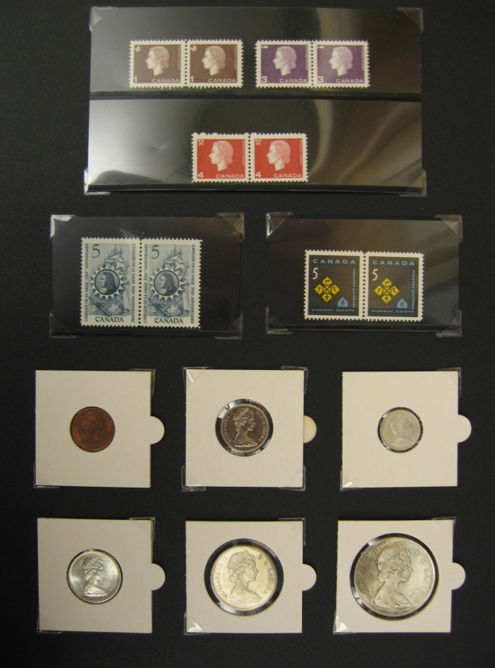 Various small coins and stamps are taped to a black sheet