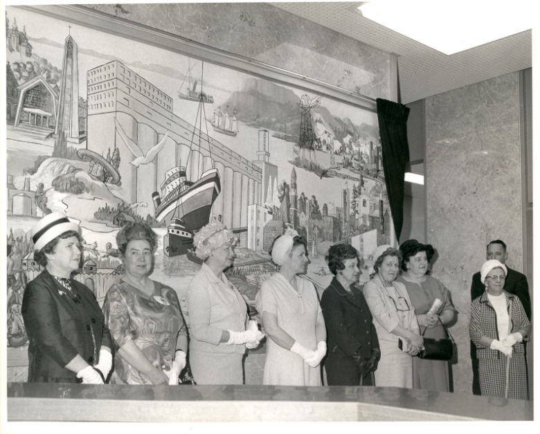 A group of people stand in front of a mural indoors wearing fancy attire