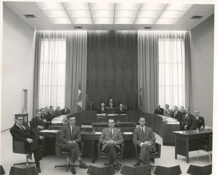 A group of people sit around a squared off table in an official council chamber
