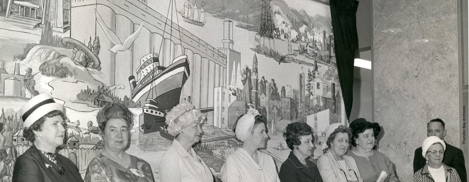 A group of women stand in front of a mural in city hall
