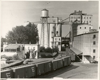 A black and white photo of a grain elevator with train caqrs in front