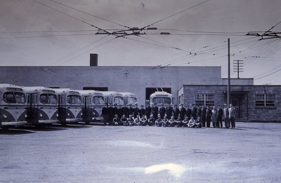 seven trolleys sit idle in a parking lot awaiting use with their driver standing infront