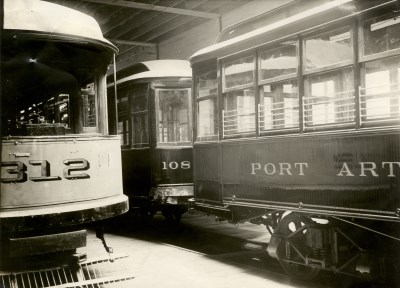 two street cars sit side by side in a large warehouse awaiting use