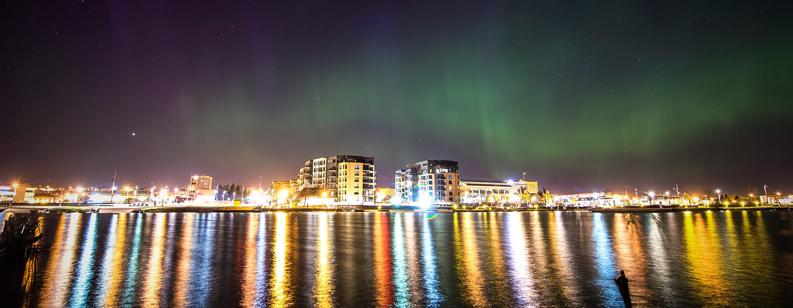 northern lights over city on waterfront