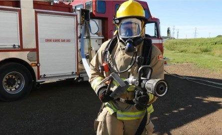 fully dressed firefighter with hose