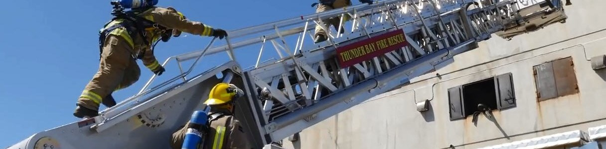 firefighters on ladder of aerial truck