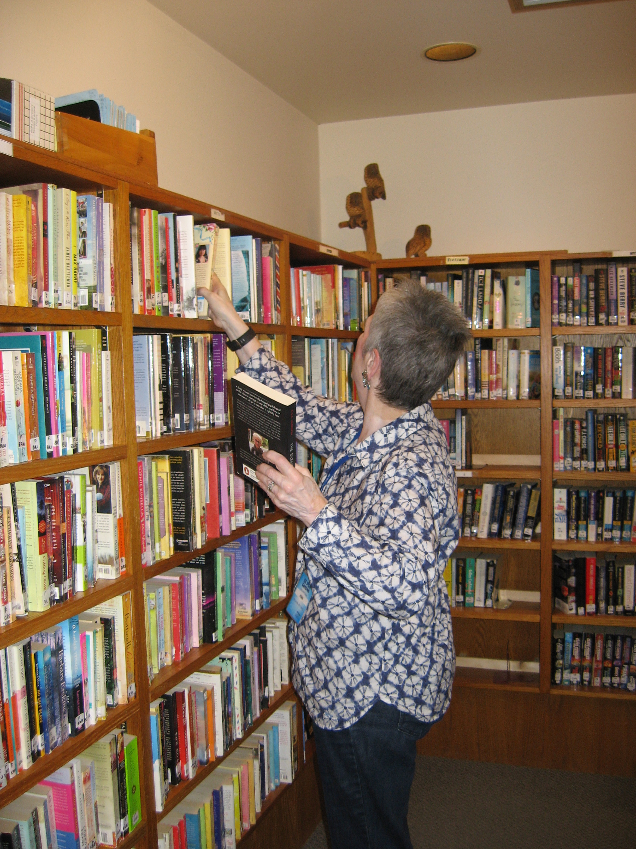 A volunteer placing a book on a shelf at the 55 Plus Centre Library.