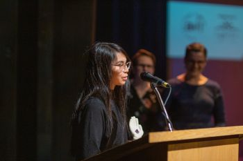 Photograph of young person at podium speaking and accepting an award
