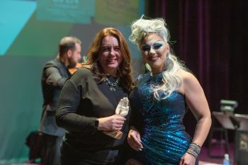 Drag queen presents award to woman on stage