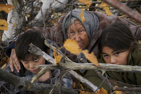 Still from the Film Indian Horse - Naomi crouches in bushes with grandsons
