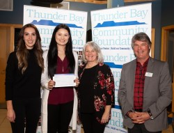 Three PRO Kids staff holding cheque with donor