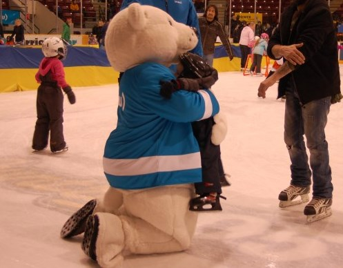 Mascot bear hugging young skater on rink
