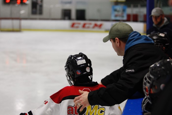 Coach directing hockey player on the ice