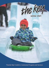 Image of child sliding down an ice slide on the cover of The Key