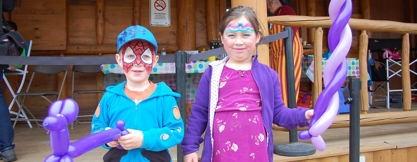kids with painted faces and balloon animals
