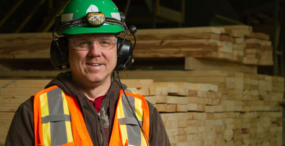 man wearing hard hat in front of lumber