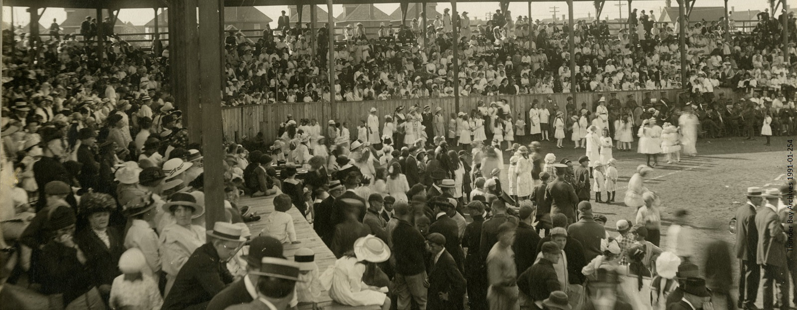 black and white photo of 1910s crowd in stadium stands